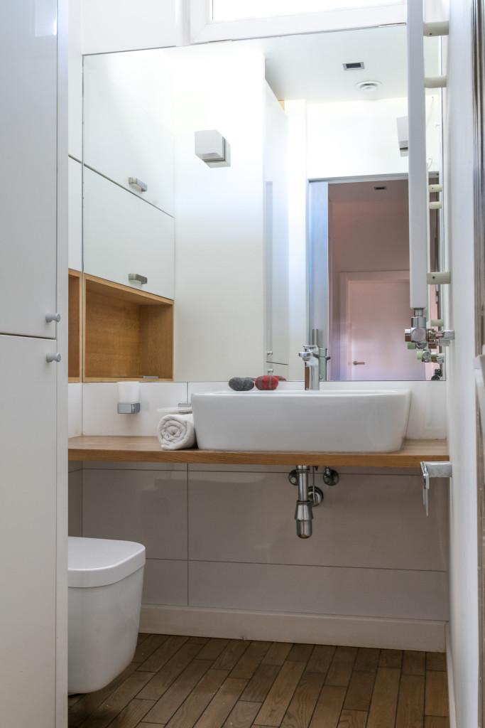 drewniany blat przy umywalce szafki w łazience mała łazienka drewno w łazience duże lustro w łazience oświetlenie w łazience