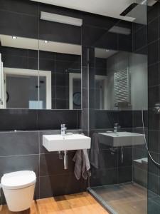 szara łazienka, czarne płytki w łazience drewno w łazience kabina prysznicowa lustro