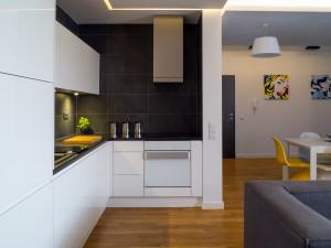 biała kuchnia pop art kuchnia z salonem kuchnia otwarta kolorowe krzesła czarne płytki w kuchni, open space, jadalnia wypoczynek