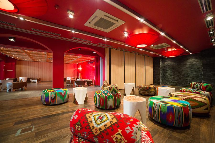 kolorowe pufy recepcja wnętrza hotel wyraziste kolory we wnętrzu styl ludowy folk wełna ekologiczne materiały drewno czerwone wnetrza