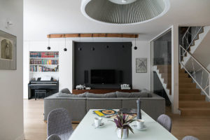 nowoczesna kuchnia folkowe biblioteczka poduchy Jacek Tryc Projektowanie wnętrz Architekt Warszawa dobry architekt Aranżacja wnętrz ciekawa lampa sufitowa meble na wymiar dom na Żoliborzu pianino stól krzesła sofa kanapa mapa balustrada