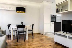 Elegancka kawalerka. Biały stół, czarne krzesła. Biała kuchnia. Meble na wymiar. Nowoczesne projektowanie ładne wnętrza salon z kuchnią