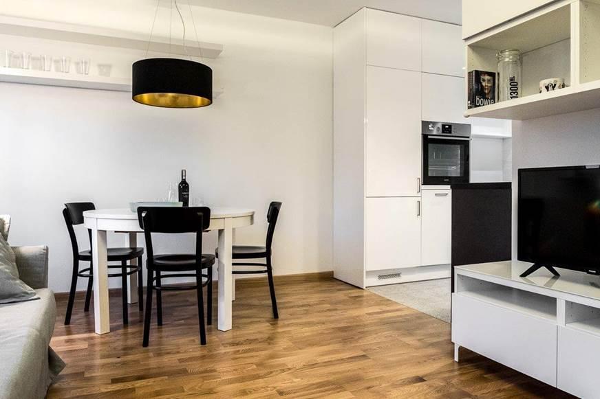 Wnętrza biało - czarne. Elegancka kawalerka. Biały stół, czarne krzesła. Biała kuchnia. Meble na wymiar. Nowoczesne projektowanie ładne wnętrza salon z kuchnią