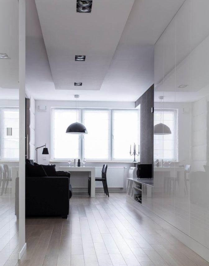 wnętrza biało - czarne pokój dzienny biały stół czarne krzesła kreatywny architekt wnętrz Jacek Tryc projektowanie aranżacja ciekawe rozwiązania w domu burzę ścianę szukam architekta