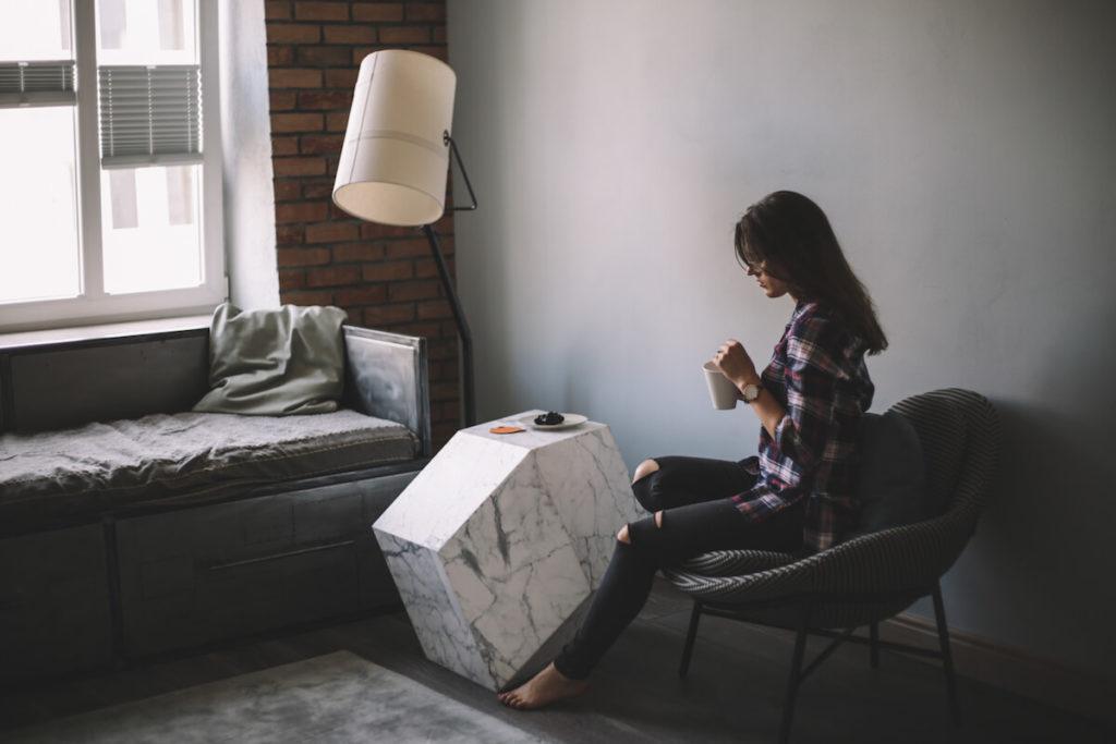Dziewczyna w pokoju. Pije harbatę. Klimatyczny stolik. Cegła na scianie. Fajna lampa. Nowoczesne wnętrza. Wygodny fotel.