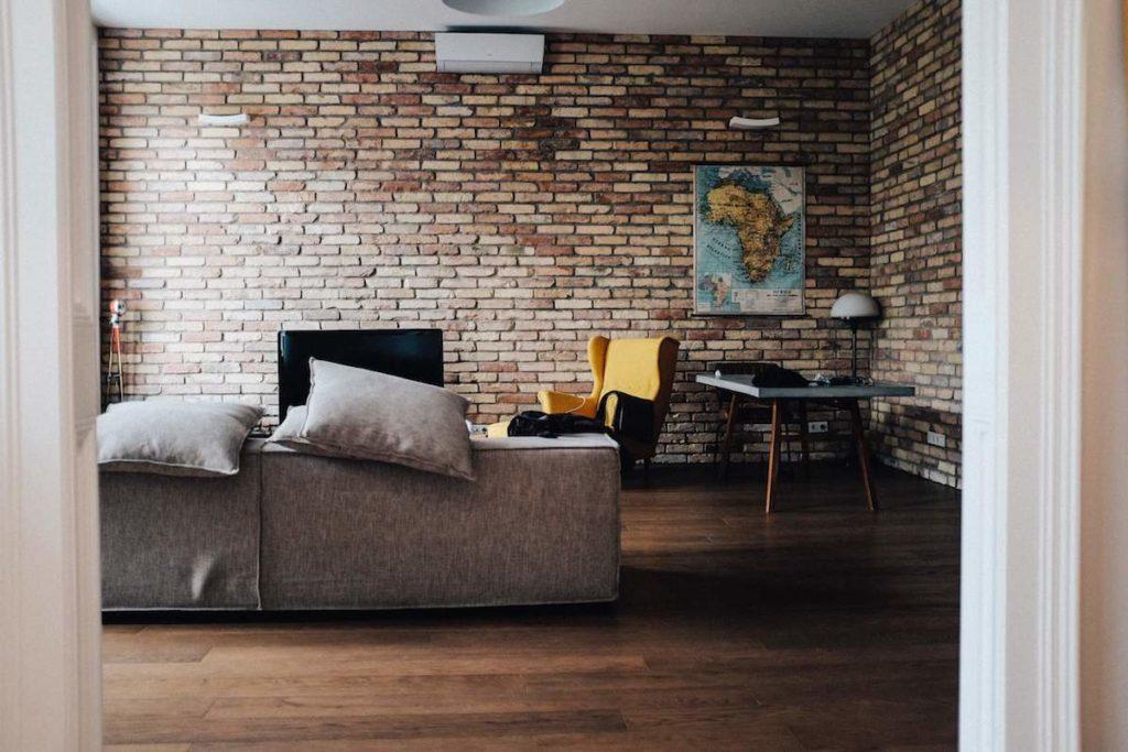 Nowoczesne wnętrza, żółty fotel, ładna kanapa. Ściana z cegły. mapa na ścianie. Kącik telwizyjny. Dom to azyl po pracy, trudach dnia
